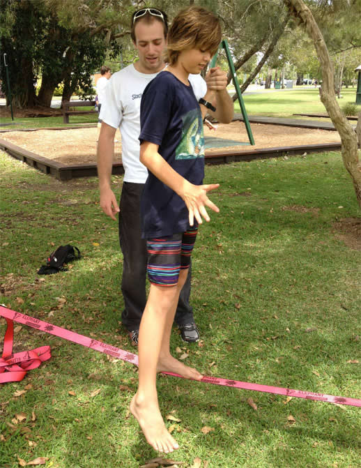 Max gets a hand from Dom as he tries balancing on the slackline for the first time
